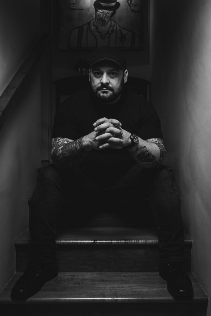 Black and white photo of Christian Picciolini sitting on stands with hands clasped together