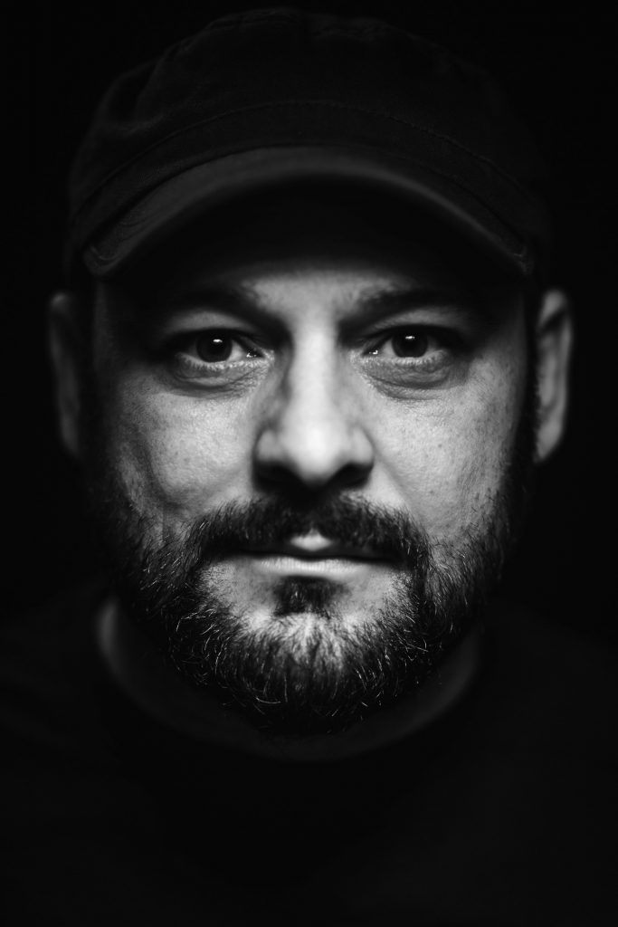 Black and white headshot of Christian Picciolini wearing a black hat