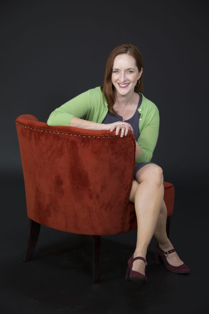 Rebecca Makkai sitting on the side of a red velvet chair