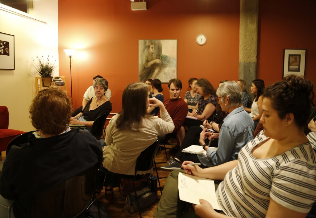 A group of writers sitting in rows in a room with an orange wall and floor lamp