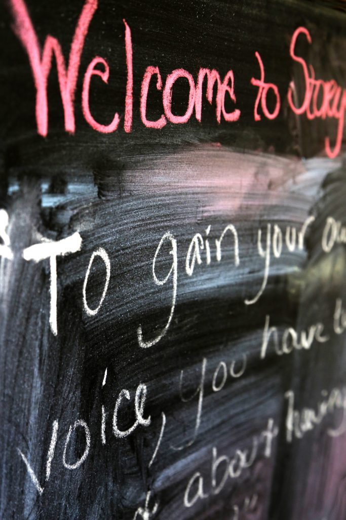 """A chalkboard with the words """"Welcome to Story"""" written in pink above white text"""