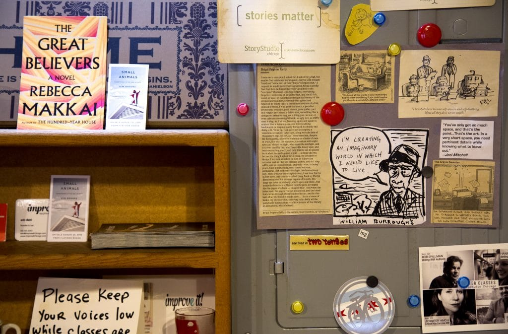 """A bookstore shelf and wall wth various newspaper clippings and a copy of """"The Great Believers"""" on display"""